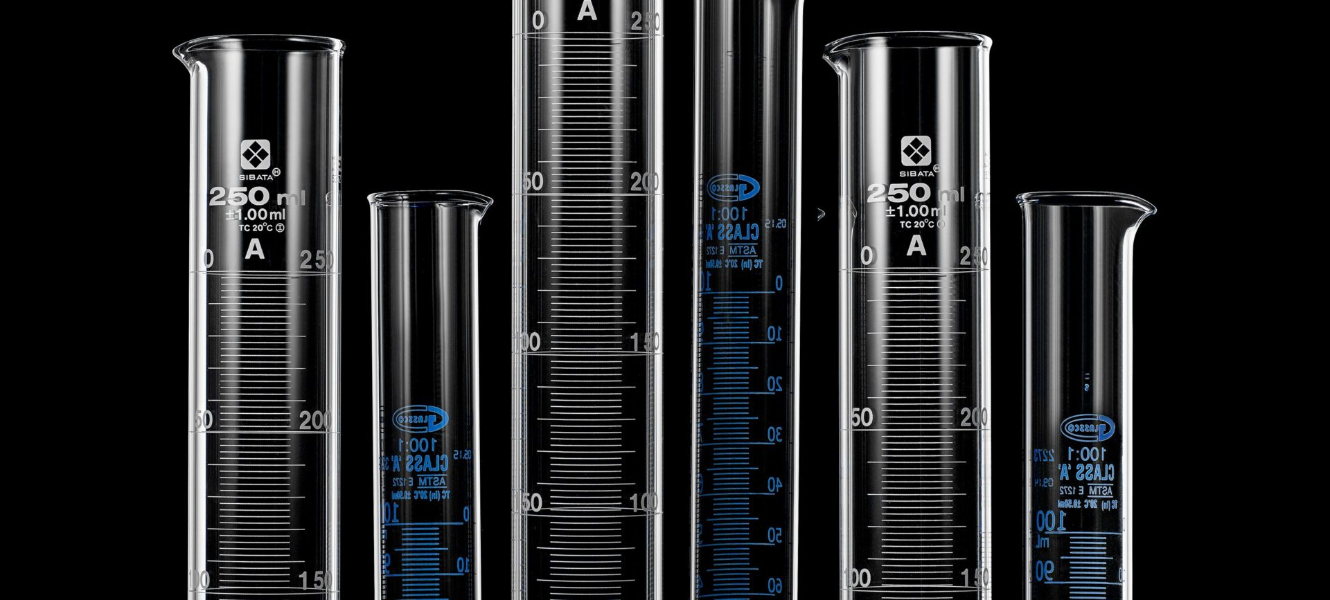 Six graduated cylinders of various sizes on a black background.