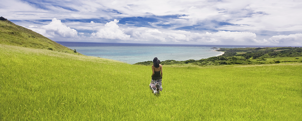 Woman walking in grass near ocean --- Image by © Ocean/Corbis